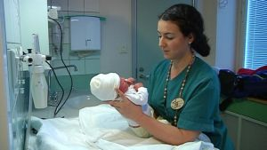 Kätilö pukee vastasyntynyttä vauvaa.