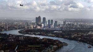 Maisemakuva Lontoosta. Kuvassa keskialalla on rykelmä Itä-Lontoossa sijaitsevan Canary Wharfin finanssikeskuksen pilvenpiirtäjiä. Taivas on pilvinen. Kuvassa ylävasemmalla lentää helikopteri. Thamesjoki kiemurtelee kuvassa oikeasta alalaidasta vasemmalle, jossa se tekee mutkan ja etenee oikealle Canary Wharfin pilvenpiirtäjien editse kunnes jossain näkymättömissä taas tekee käännöksen vasempaan. Joella kulkee laivoja.