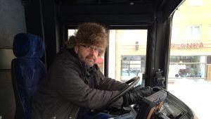 Linja-autonkuljettaja ratin takana karvahattu päässä, talvitakki päällään ja rukkasen kädessä.