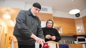 Ghassan ja Iman sytyttävät kynttilää keittiössä.