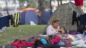 Nainen avaa lääkepulloa sylissään makaavalle pikkupojalle. Taustalla kupolitelttoja ja pyykkinaru.