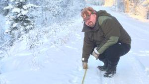 Aleksi Anttila mittaa tuoreita suden jälkiä Perhon Pässikankaalla.