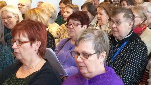 Koululaulutilaisuudeen osallistuva yleisö laulaa vanhoja koululauluja Tampereella Työväenmuseo Werstaalla.