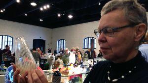 Nainen pitää maljakkoa kädessään Lasipäivä-tapahtumassa
