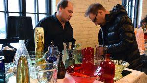 Kaksi miestä tarkastelee lasiesineitä