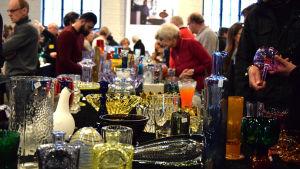 Ihmisiä tutustumassa myynnissä oleviin lasiesineisiin
