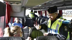 Poliisi tarkastaa junavaunussa nuoren naismatkustajan henkilöllisyystodistusta. Taistalla toinen poliisi ja muita matkustajia.