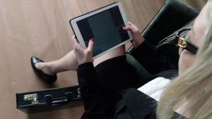 Nainen käyttää tablet-tietokonetta.