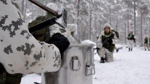 Sotilas odottaa ruokaa korkeassa polviasennossa.