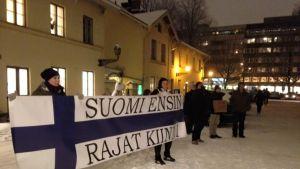 Rajat kiinni! -mielenosoittajia Turun kaupunginvaltuuston ulkopuolella.