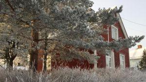Punainen omakotitalo lumisessa maisemassa.