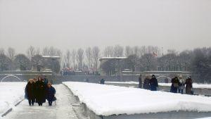 Mustiin pukeutuneet ihmiset kävevät lumisella Leningradin piirityksen uhrien muistolle perustetulla hautausmaalla harmaassa Pietarissa.