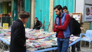 Kirjakauppias Abdurrahman Emad haluaisi elää normaalia, rauhallista elämää. Kuva kadulta, missä kirjakauppias keskustelee iäkkään asiakkaan kanssa.