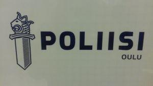 Oulun poliisilaitoksen kyltti valkoisella pohjalla ja sininen teksti.