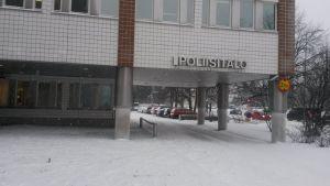 Talvinen kuva Oulun poliisitalosta ja parkkipaikalta, jossa autoja.