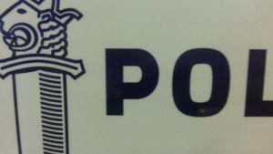 Osa tekstiä ja poliisimerkkiä valkoisella pohjalla.