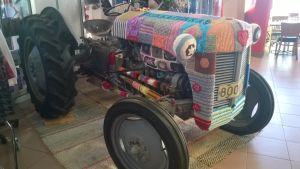 Virkatuilla ja neulotuilla tilkuilla koristeltu traktori.