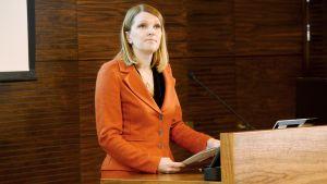 Mari Kiviniemi puhuu OECD:n maaraportin julkistamistilaisuudessa Helsingissä.