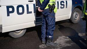 Poliisi seisoo poliisiauton edustalla.