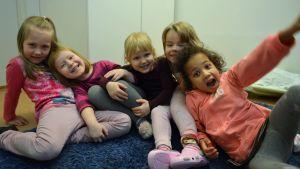 Viisi tyttöä istuu ja nauraa lattialla.