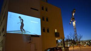 videotaidetta kadulla poliisitalon seinässä