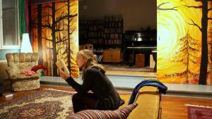 Ilona Tapanainen lukee Sun Ahonlaidan olohuoneessa sohvalla istuen.