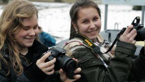 Kaksi teinityttöä kameroiden kanssa