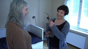 Lilli Haapala (oik.) esittelee taideteostaan Camilla Edström Odemarkille.