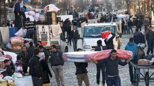 Pakolaisia kantamassa tavaroitaan Diyarbakirissa.