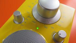 Keltainen radiovastaanotin oranssia taustaa vasten kuvattuna.