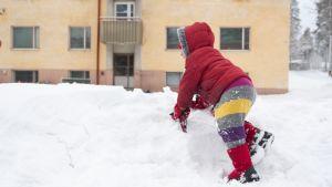 Nuori turvapaikanhakija leikkii lumessa.