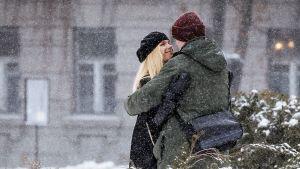 Pariskunta halaa lumisessa puistossa.