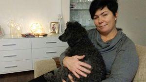 Ulla Hagkvist istuu sylissään musta koira.