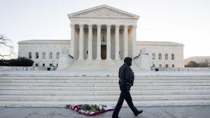 Poliisiviranomainen kävelee Antonin Scalian muistopaikan ohitse korkeimman oikeuden edustalla Washingtonissa 14. helmikuuta 2016.