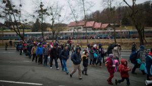 Junalla saapunut väkijoukko kulkee radan vartta pitkin, joukossa on useita lapsia.