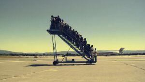 paljon ihmisiä yksinään seisovilla lentokoneen rappusilla