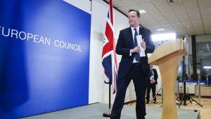 Cameron puhujankorokkeen vieressä paperin kanssa, astumassa pois korokkeen luota. Taustalla näkyy Britannian lippu ja seinätaulu, jossa lukee European Council.