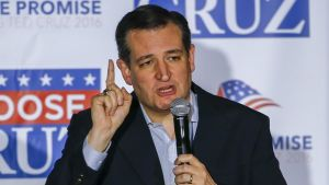 Ted Cruz puhuu mikrofoniin osoittaen oikean kätensä etusormella ylöspäin. Hänellä on tumma puku, kauluspaita mutta ei kravattia. Taustalla on Cruzin kampanjajulistetta.