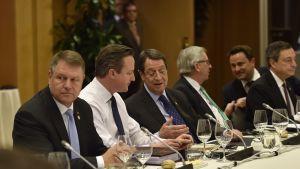 Joukko valtionpäämiehiä ja EU:n korkeita virkamiehiä istuu pöydän takana ja keskustelee. Britannian pääministeri David Cameron on paitahihasillaan, kravatti kaulassa, muilla herroilla on puvuntakit päällä.