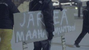 Katupartiolainen kantaa kylttiä, jossa vaaditaan järkeä maahanmuuttoon