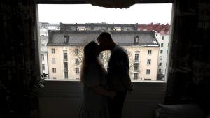 Pariskunta suutelee ikkunan edessä.