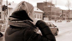 Nainen seisoo liikenteen edessä sormet korvien päällä.