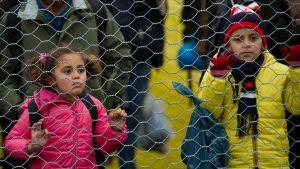 Pieni vaaleanpunaisiin puettu lettipäinen tyttö ja hieman isompi keltatakkinen poika pitävät kiinni verkkoaidasta.