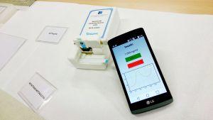 Kuvassa mittalaite jonne on laitettu sylkinäyte. Mittaustulos näkyy kännykkäsovelluksessa.
