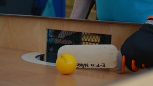 Pallo on kova ja sen sisällä on hauleja, jotka kolisevat sen liikkuessa. Maila on puinen ja kättä suojaa paksu hanska.