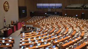 Naisedustaja pitää puhetta Etelä-Korean parlamentissa tyhjälle salille.