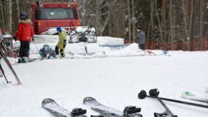 Sukset lumella. Taustalla laskettelijoita