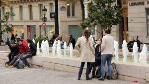 Opiskelijoita Pariisissa, istumassa pienen suihkulähteen äärellä.