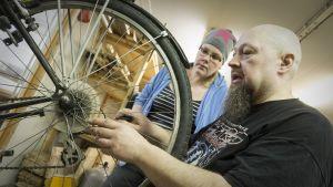 Työpajaohjaaja Jari Haapaniemi näyttää Tiina Vehkalammelle, kuinka polkupyörän takavaihtajaa säädetään.