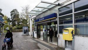 Rollaattoria työntävä vanha nainen ja kännykkään puhuva teinipoika Husbyn metroasemalla.